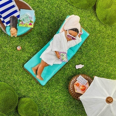 Doll on lounge chair outside.