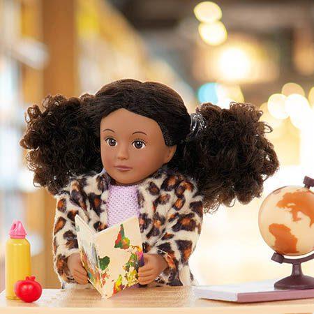 Mini doll reading a book.