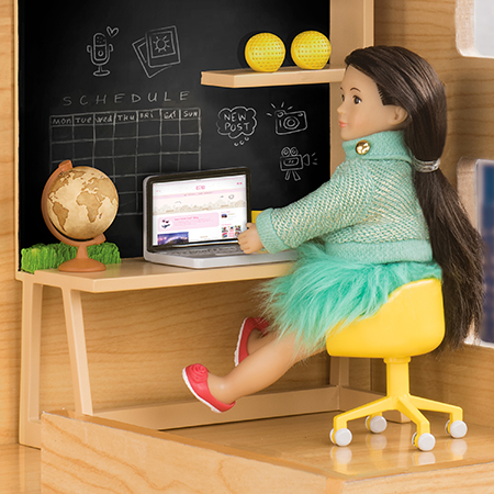 Mini doll sitting at a desk.