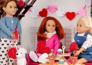 Three dolls making heart crafts.