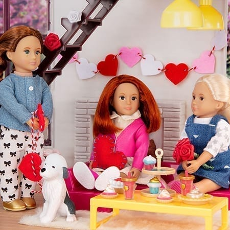 Three dolls making heart crafts.
