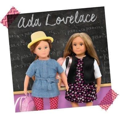 Mini dolls in front of blackboard with Ada Lovelace written on it.